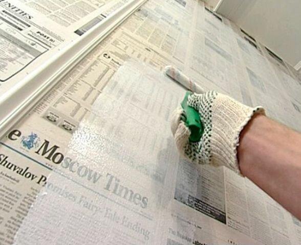 Нанесите клей на стену и наклейте газеты.